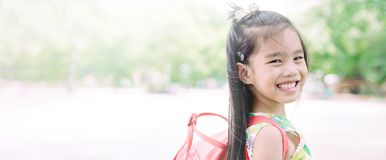 Happy asian girl arriving school from home with a backpack.  royalty free stock photography