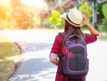 Happy Asian girl backpack in the road and forest background. Relax time on holiday concept travel Stock Photos