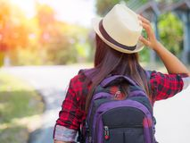 Happy Asian girl backpack in the road and forest background. Relax time on holiday concept travel ,color of vintage tone and soft focus Royalty Free Stock Photography