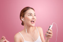 Happy asian girl dancing and listening to the music isolated on Stock Images