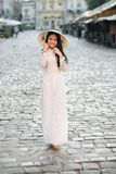 Happy asian girl dressed in traditional Ao Dai white dress with vietnamese conical hat Non La, Leaf Hat. Asian girl walks on the street at cityspace background stock images