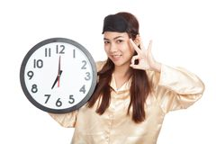 Happy Asian girl with eye mask and clock show OK sign Stock Photo