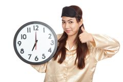 Happy Asian girl with eye mask and clock show thumbs up Stock Photography