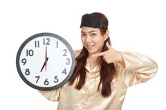 Happy Asian girl with eye mask point to a clock Stock Photo