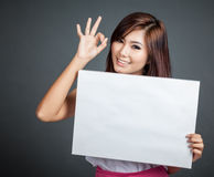 Happy Asian girl hold blank sign show OK sign. On gray background Stock Image