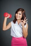 Happy Asian girl hold a dumbbell show Ok sign Stock Images