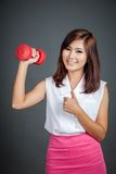 Happy Asian girl hold a dumbbell show thumbs up Stock Photos