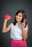 Happy Asian girl hold a dumbbell show vicrtory sign Royalty Free Stock Image
