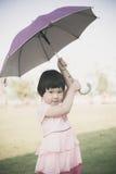 Happy Asian girl holding umbrella outdoor. Stock Photos