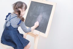 Happy asian girl kid draw cartoon with chalk on blackboard. For learning at home. Photo for kid education and school study concept Stock Photo