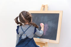 Happy asian girl kid draw cartoon with chalk on blackboard Stock Image