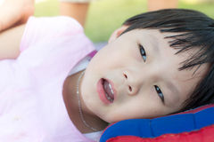 Happy Asian girl laying with pillow outdoor. Stock Photo