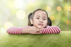 Happy asian girl lean on the green grass. At outdoor Stock Image