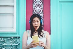 Happy Asian girl listening to music with headphones outdoor - Young Chinese woman playing her favorite playlist music stock photography