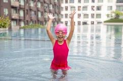 Happy asian girl love swimming pool. Kid wearing pink swimming suite on water. Sport kid activities concept. Outdoor activities in summer Stock Photo