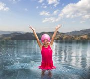 Happy asian girl love swimming pool. Kid wearing pink swimming suite on water. Sport kid activities concept Royalty Free Stock Photos