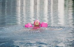 Happy asian girl love swimming pool. Kid wearing pink swimming suite on water. Sport kid activities concept Royalty Free Stock Image