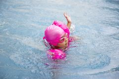 Happy asian girl love swimming pool. Kid wearing pink swimming suite on water. Sport kid activities concept Royalty Free Stock Photo