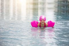 Happy asian girl love swimming pool. Kid wearing pink swimming suite on water. Sport kid activities concept Stock Image