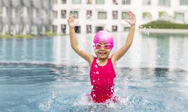 Happy asian girl love swimming pool. Kid wearing pink swimming suite on water. Sport kid activities concept Royalty Free Stock Photography