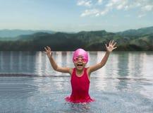 Happy asian girl love swimming pool. Kid wearing pink swimming suite on water. Sport kid activities concept. Outdoor activities in summer Stock Photography