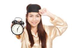 Happy Asian girl  in pajamas show alarm clock Stock Photo