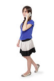 Happy Asian girl on phone walking. Happy Asian teenage girl talking on her phone and walking, full body isolated on white background Royalty Free Stock Photo