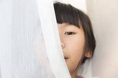 Happy Asian girl playing curtain at home. Stock Images