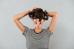Happy asian girl playing with her hair and showing tongue stock photos