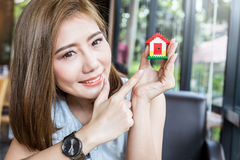 Happy asian girl point to house model Royalty Free Stock Image