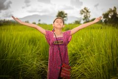 Happy Asian girl raising arms in green rice field, countryside o Stock Photography