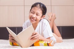 Happy Asian girl reading a book in her bed Royalty Free Stock Photo