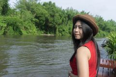 Happy Asian girl red shirt and brown hat on the river in nature. Background, Relax time on holiday concept travel., Thailand river kwai and typical landscape Stock Images