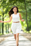Happy Asian girl. Running in summer / spring park joyful and smiling in white sundress around trees. Beautiful fresh multiracial Asian Caucasian woman female Stock Image