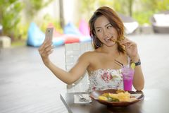 Happy Asian girl in dress having brunch or lunch at holiday resort outdoors taking selfie pic with mobile phone Royalty Free Stock Image