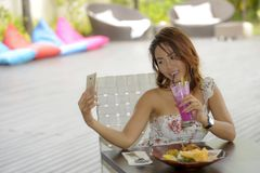 Happy Asian girl in sexy dress having brunch or lunch at holiday resort outdoors taking selfie pic with mobile phone Royalty Free Stock Image