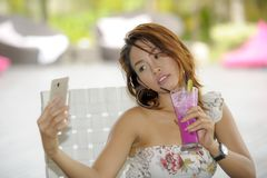 Happy Asian girl in sexy dress having brunch or lunch at holiday resort outdoors taking selfie pic with mobile phone Stock Image