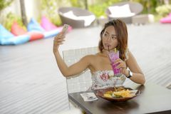 Happy Asian girl in sexy dress having brunch or lunch at holiday resort outdoors taking selfie pic with mobile phone Royalty Free Stock Photography