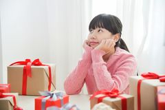 Happy Asian girl smiling and thinking with gift boxes. Stock Image