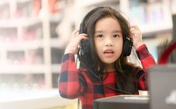 Happy asian girl student listening to music with headphones royalty free stock image