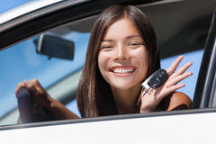 Happy Asian girl teen driver showing new car keys. Young woman smiling driving new car holding key. Interracial ethnic woman driver holding car keys driving stock photo