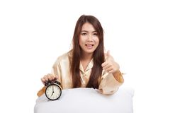 Happy Asian girl  thumbs up  with pillow and alarm clock Royalty Free Stock Image