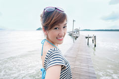 Happy asian girl to the sea. A happy Asian girl on a wooden bridge in a sea Stock Photography
