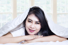 Happy asian girl under blanket in bed Royalty Free Stock Photos