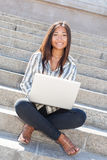Happy asian girl using a laptop outdoor Stock Image