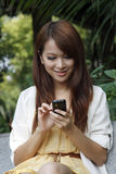 Happy asian girl using mobile phone. A happy girl using mobile phone outdoor Stock Images
