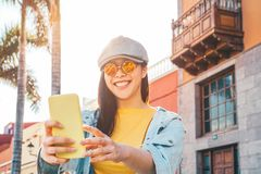 Happy Asian girl using mobile smartphone outdoor - Chinese social influencer having fun making video story for new trends social royalty free stock photo