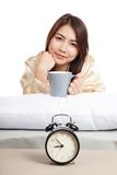 Happy Asian girl  wake up  with alarm clock and  coffee cup Royalty Free Stock Images