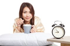 Happy Asian girl  wake up  with alarm clock and  coffee cup Royalty Free Stock Photos