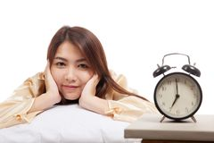 Happy Asian girl wake up with alarm clock. Isolated on white background royalty free stock images